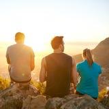 Amis sur une hausse appréciant le lever de soleil ensemble Photo stock