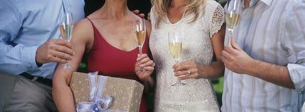 Amis tenant Champagne Flutes Image libre de droits