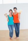 Amis tenant des échantillons de pinceau et de couleur dans une nouvelle maison Photo libre de droits