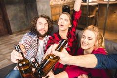 Amis tenant des bouteilles à bière Photo stock