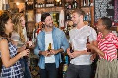 Amis tenant des bouteilles à bière dans le bar Photos stock