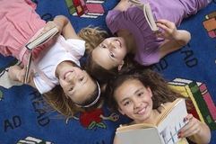 Amis tenant des livres tout en se trouvant sur le tapis Image stock