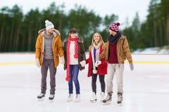 Amis tenant des mains sur la piste de patinage extérieure Photographie stock libre de droits