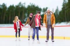 Amis tenant des mains sur la piste de patinage extérieure Photos stock