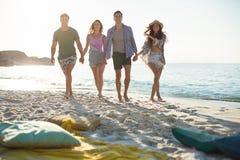 Amis tenant des mains tout en marchant à la plage Photo stock