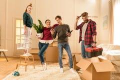 Amis tenant différentes choses pour entrer dans la nouvelle maison Image stock