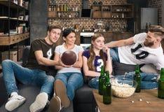 Amis tenant la boule de rugby et regardant l'un l'autre Image stock