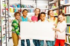 Amis tenant la feuille de livre blanc dans la bibliothèque Photo stock