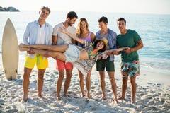 Amis tenant la jeune femme tout en se tenant sur le rivage à la plage Image stock