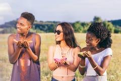 Amis tenant la peinture colorée dans des mains au festival de holi Image libre de droits