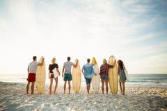 Amis tenant la planche de surf sur la plage Photographie stock libre de droits