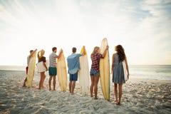 Amis tenant la planche de surf sur la plage Photos stock