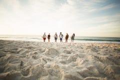 Amis tenant la planche de surf sur la plage Image libre de droits