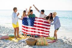Amis tenant le drapeau américain sur le rivage à la plage photos libres de droits