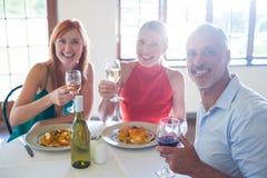 Amis tenant le verre de vin tout en ayant le repas Photo stock