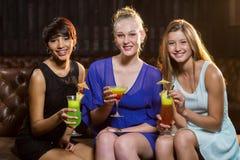 Amis tenant le verre du cocktail dans la barre Photographie stock