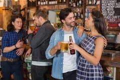 Amis tenant le verre et la bouteille de bière par le compteur dans le bar Images stock