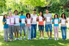 Amis tenant les papiers blancs en parc Photographie stock libre de droits