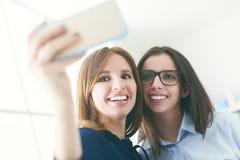 Amis tirant des photos d'individu avec un mobile Images libres de droits