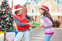 Amis tirant le cadeau de Noël Photos libres de droits
