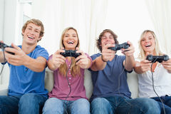 Amis tous jouant des jeux vidéo ensemble Photo stock