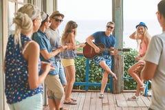 Amis traînant des vacances à un vieux porche en bois de carlingue par la mer tandis que l'un d'entre eux joue la guitare et d'aut Photos libres de droits