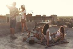 Amis traînant sur un dessus de toit de bâtiment Images stock