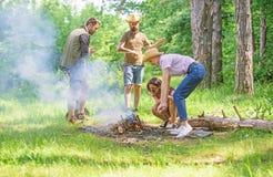 Amis travaillant comme équipe pour garder le feu La forêt de camping de société préparent le feu pour le pique-nique Ajoutez du b photos stock