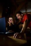 Amis travaillant sur un ordinateur portatif Photographie stock