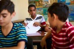 Amis trichant pendant l'essai à l'étude d'école et d'étudiants Images libres de droits