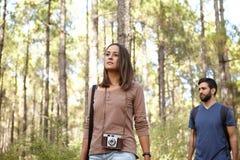 Amis trimardant dans une forêt de pin Photo stock