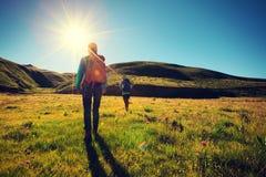 amis trimardant en montagnes de lever de soleil Photographie stock libre de droits