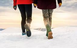 Amis trimardant sur le sommet de montagne couvert de neige Photo stock