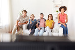 Amis tristes regardant la TV à la maison Images stock