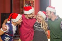 Amis utilisant des chapeaux de Noël regardant l'un l'autre Image stock