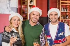 Amis utilisant des chapeaux de Noël souriant à l'appareil-photo Photo stock