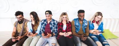 Amis utilisant le smartphone sur le sofa au lieu de rendez-vous d'intérieur - les gens groupez adonné par le téléphone intelligen image stock