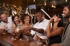 Amis versant le champagne à une nouvelle partie du ½ s de ¿ de Yearï à une barre Photos libres de droits