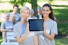 Amis volontaires heureux montrant l'écran de PC de comprimé Image stock