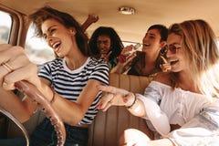 Amis voyageant dans la voiture et ayant l'amusement Images libres de droits