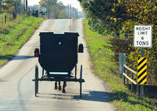 Amish buggy. A black Amish buggy traveling on a country road Stock Image
