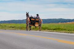 Amish Carriage Along Pennsylvania Road. Horse drawn Amish buggy traveling down Pennsylvania road Stock Photos