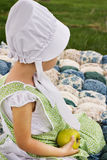 Amish child. Amish toddler sitting on a handmade quilt with an apple in her hand Stock Photos