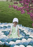 Amish child. Sitting on a handmade biscuit quilt under a flowering Crab Apple tree Stock Image