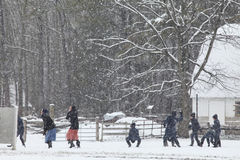 Amish Children having a snowball fight. Amish children- boys and girls having a snowball fight outside in their schoolyard in rural Delaware stock images