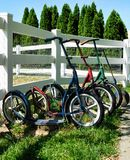 Amish children`s scooters. Four amish chidlren`s scooters waiting by the fence outside the one room schoolhouse stock photos