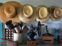 Amish Country Farm Hats, Pantry. Kitchen pantry scene with an old country Amish farm style. Old straw hats hang above a set of antique kitchen items and utensils stock photo