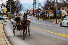 Amish deux roulent dedans le village de rapports Photo libre de droits