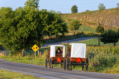 Amish Families Travel With Horse and Carriage. MILROY PENNSYLVANIA - September 4, 2016: Amish families travel with horse and carriage on a winding rural road in Royalty Free Stock Photos