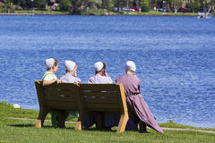 Amish girls sitting by the lake. 4 Amish girls sitting on a bench by the lake Royalty Free Stock Photos